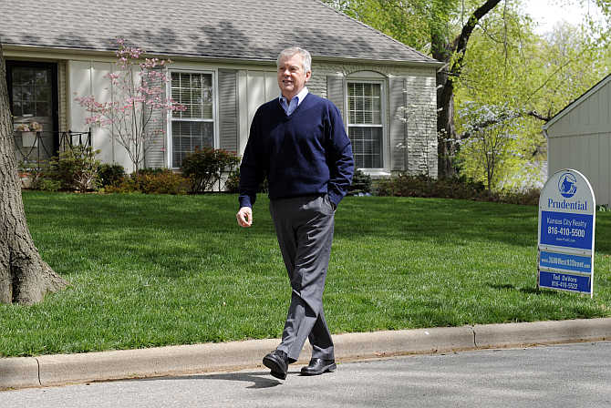 Ted DeVore, a senior sales executive with Prudential, walks back to his car after placing for sale sign in Leawood, Kansas, United States.