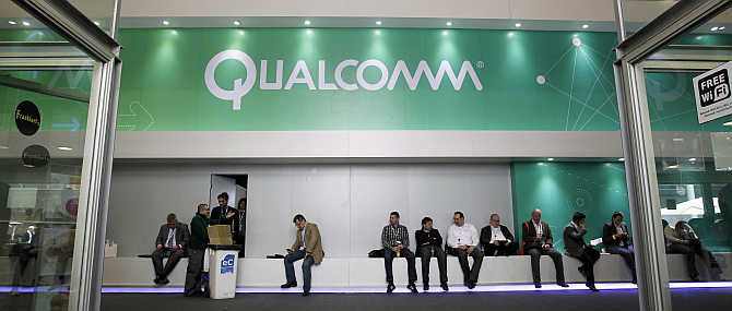 People sit next to a Qualcomm stand at the Mobile World Congress in Barcelona, Spain.