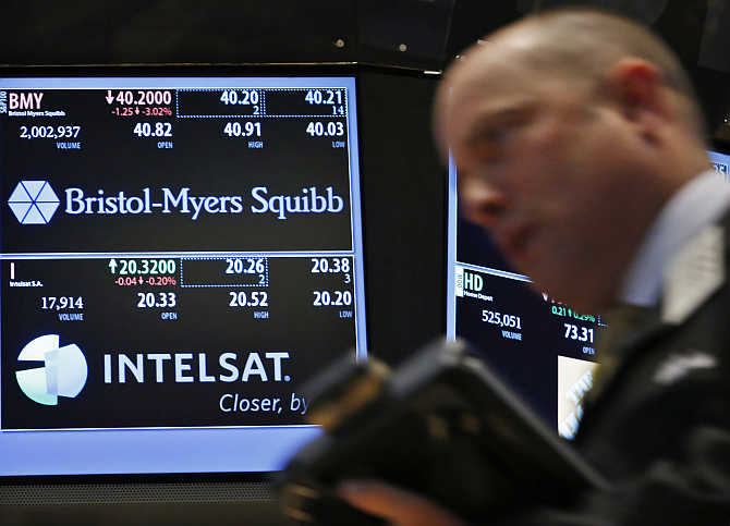A trader passes by a screen displaying the tickers symbols for Bristol-Myers Squibb on the floor at the New York Stock Exchange.