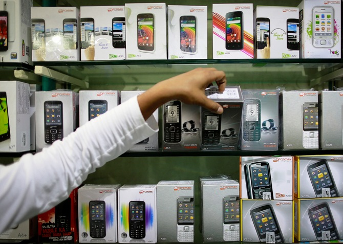 An employee takes out a Micromax mobile phone from the display at a mobile store in Mumbai.