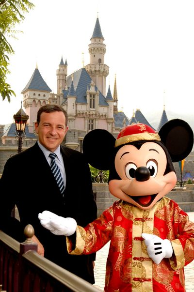 Bob Iger, Chairman and Chief Executive Officer, of the Walt Disney Company, stands next to Mickey Mouse in front of Sleeping Beauty Castle.