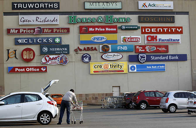 A man loads groceries into his car as logos of shops are seen on a wall at a mall in Lenasia, south of Johannesburg, South Africa.
