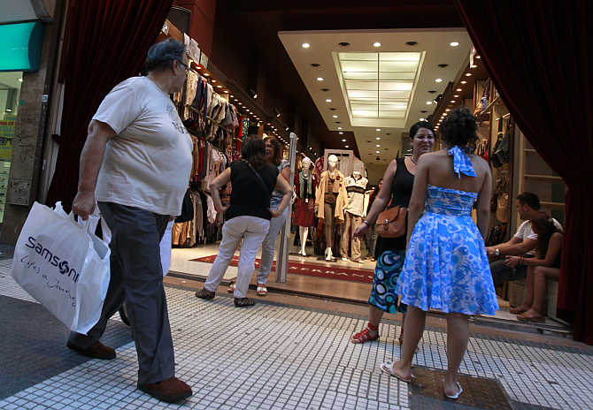 A man walks past a clothing store in Buenos Aires, Argentina.