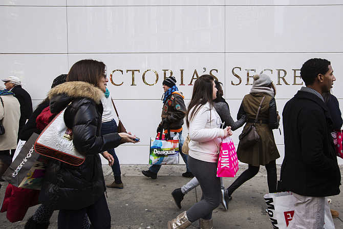 Pedestrians carrying shopping bags walk past a Victoria's Secret store in New York.