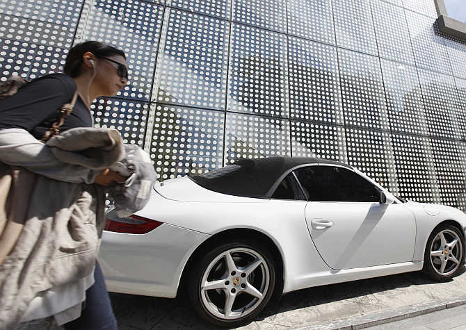A woman walks past a Porsche on the Garosugil, or the Tree-Lined Street, in the Gangnam area of Seoul, South Korea.