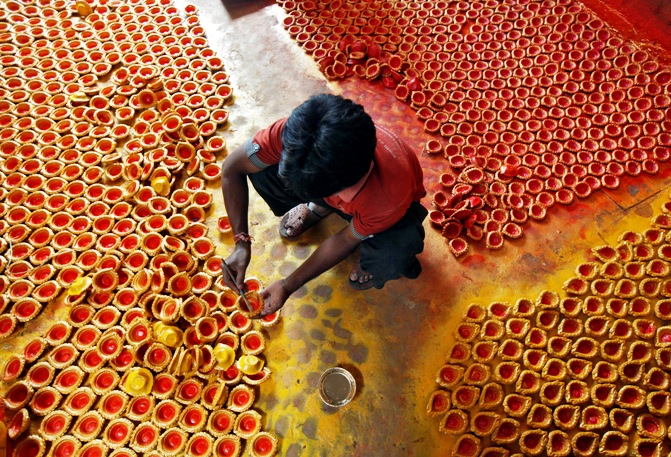 A worker paints earthen lamps in Kolkata.