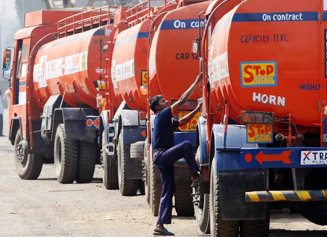 An employee of a petroleum company climbs onto a truck carrying petroleum products in Mumbai.