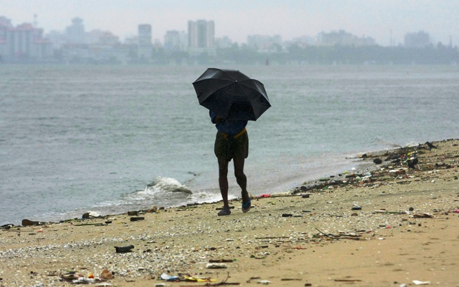 A man strolls along the Fort Kochi beach while holding an umbrella during a rain shower.