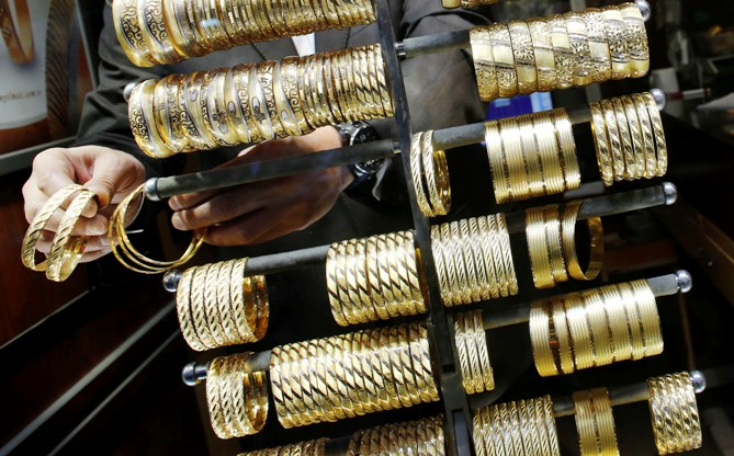 A goldsmith arranges gold bangles at a jewellery shop.