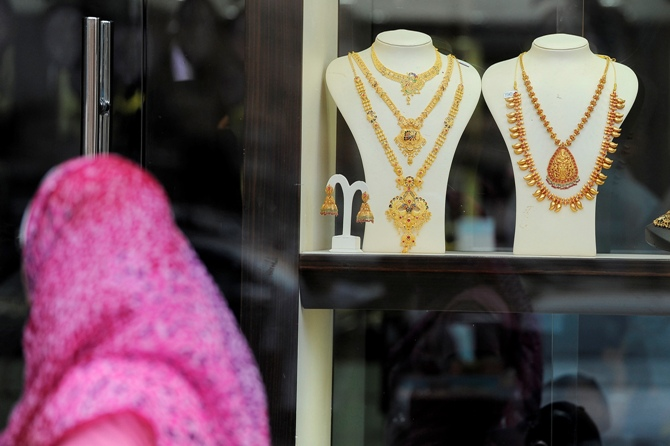 A woman walks past a window display for gold jewellery at Hamdan Street.