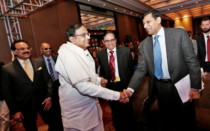 RBI Governor Rajan (2nd R) shakes hands with India's Finance Minister Palaniappan Chidambaram (3rd L) as they arrive to attend the Delhi Economics Conclave 2013 in New Delhi December 11, 2013.