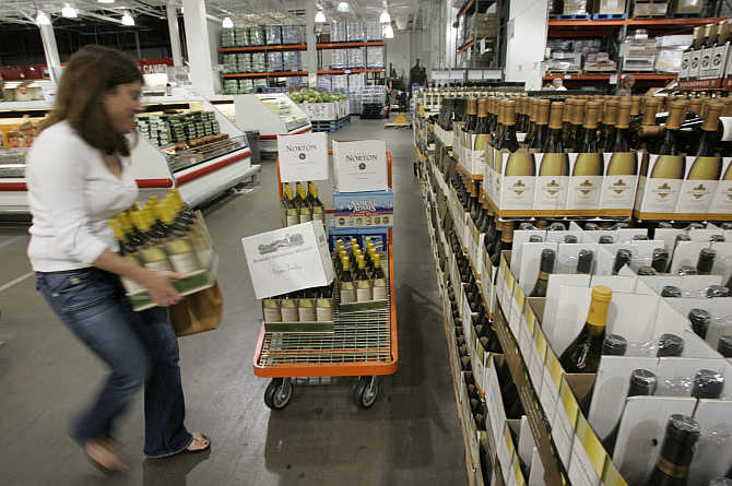 A shopper loads cartons of wine onto her cart at the Costco Warehouse in Arlington, Virginia.