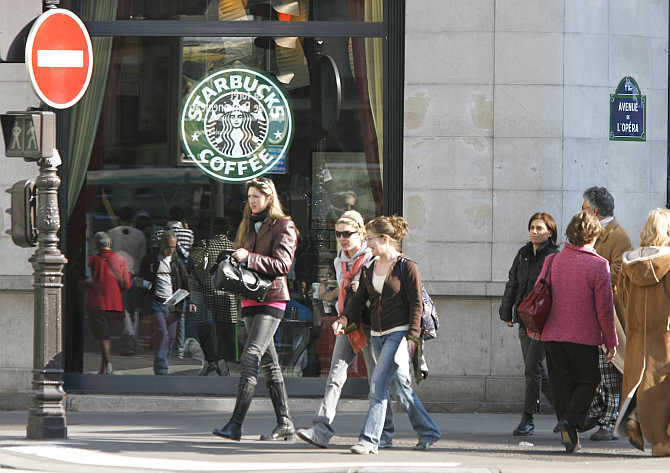 Pedestrians pass by Starbucks's coffee house in Paris.