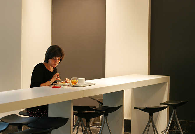 An employee takes her coffee break at a free restaurant in Santander Central Hispano's complex, Santander Group City, in Boadilla del Monte, in the outskirst of Madrid, Spain.