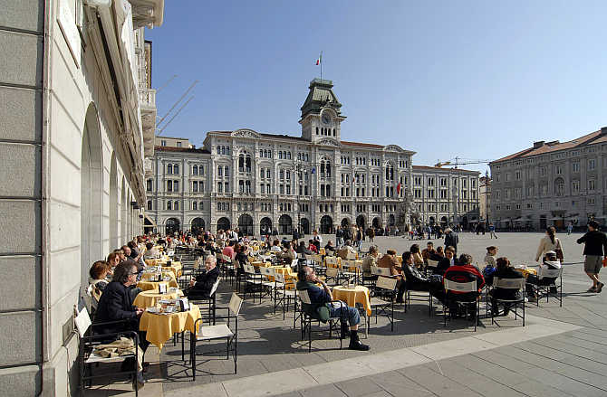 People gather at an outdoor cafe in the main square in Trieste, Italy.