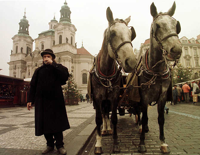 A coachman keeps himself warm by sipping a hot cup of coffee in central Prague's Old Town Square, the Czech Republic.