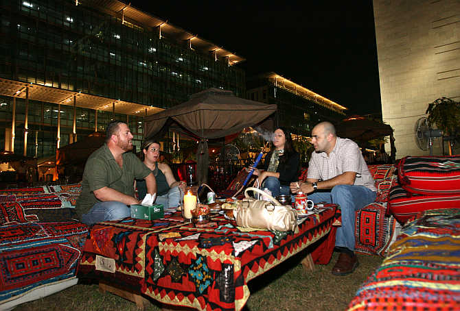 People smoke water pipes and drink coffee at Ziara Ramadan tent in Dubai, United Arab Emirates.