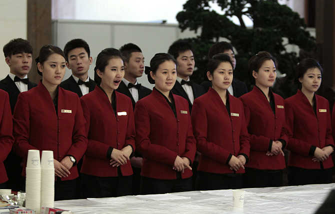 Tea attendants wait to serve delegates during the plenary meeting of the National People's Congress, China's parliament, at the Great Hall of the People in Beijing.