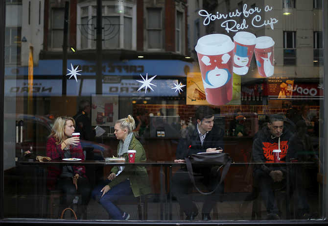 Patrons sit in a Starbucks Coffee shop in central London.