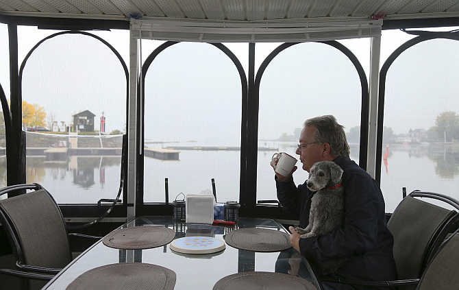 Semi-retired Ian Morton drinks his coffee while holding his dog Zoey onboard his houseboat docked at Le Port De Plaisance de Lachine, a marina in Montreal, Quebec, Canada.