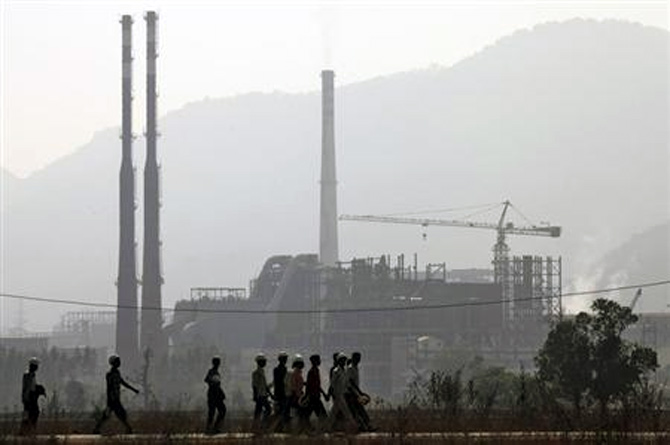 Workers walk in front of the Vedanta Aluminium factory in Lanjigarh in Orissa.