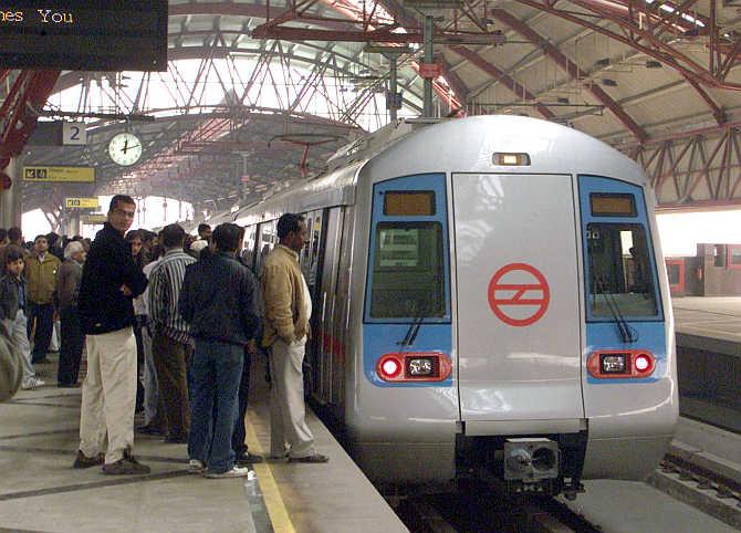 Commuters wait to board a Metro train in New Delhi.