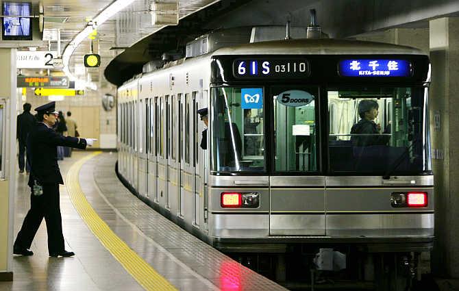 A subway worker gestures as a car at Tsukiji subway station of Tokyo Metro Hibiya Line moves off in Tokyo, Japan.