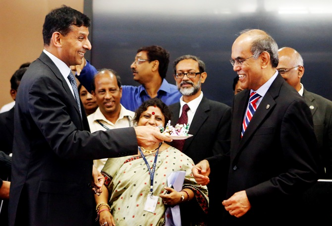 Raghuram Rajan (L), newly appointed governor of Reserve Bank of India (RBI), offers sweets to the outgoing governor Duvvuri Subbarao during the taking over ceremony at the bank's headquarters in Mumbai September 4, 2013.