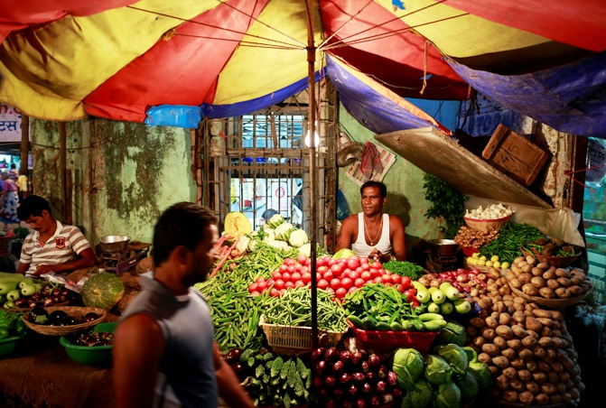 A vendor selling vegetables waits for customers at his stall at a market in Mumbai.