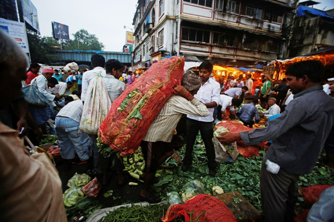 A labourer carries a sack of cabbages after unloading it from a supply truck at a vegetable wholesale market.