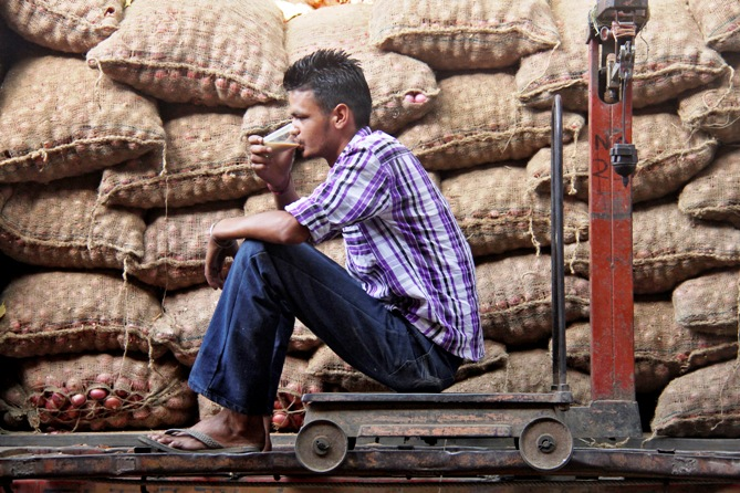 A vendor drinks tea as he sits on a weighing scale besides stacked sacks of onions at a wholesale vegetable and fruit market in Chandigarh.