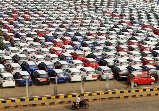 A man rides his motorbike past parked Hyundai cars ready for shipment at a port in Chennai.