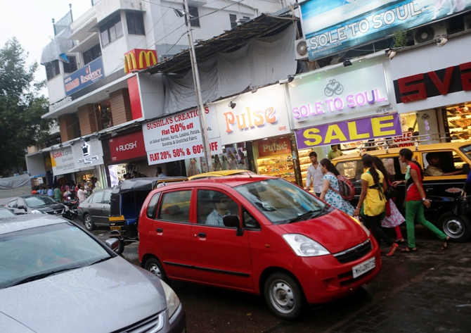 Vehicles drive past stores on a street in Mumbai.
