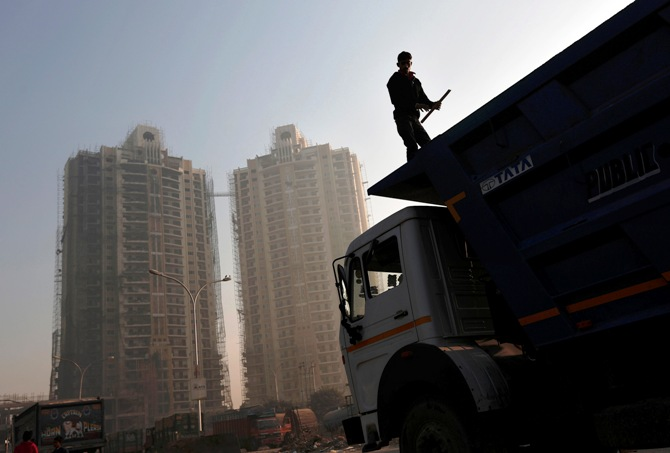 A labourer stands on a truck carrying construction materials at a construction site of residential buildings in Noida on the outskirts of New Delhi.