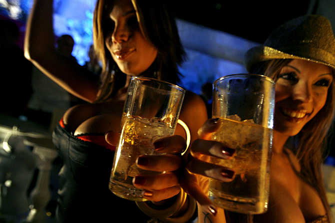 Women dance and drink whisky during a Playboy magazine party in Caracas, Venezuela.