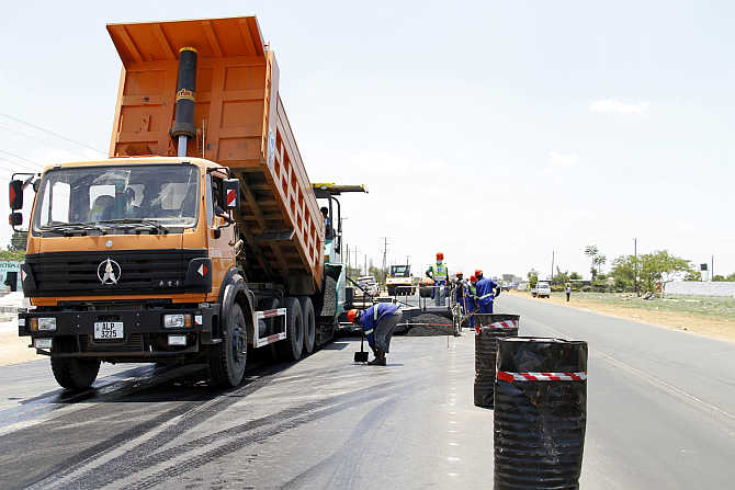 Labourers carry out surfacing work on a road near the Zambian capital Lusaka.