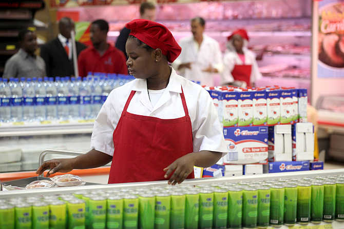 A shop assistant arranges products at the South African firm Shoprite's main store in Nigeria's commercial capital Lagos.