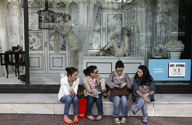 Girls sit in front of a shop window outside a department store in central Athens, Greece.