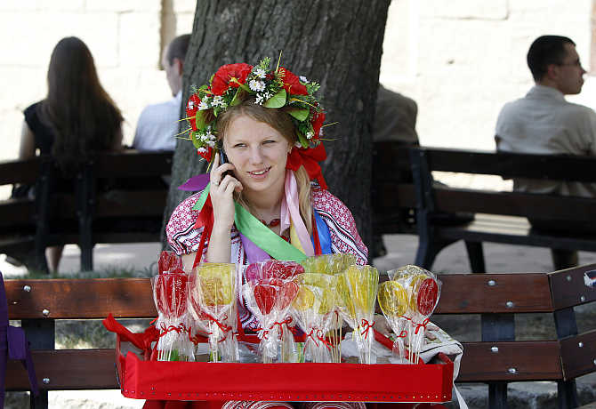 A street vendor, dressed in national costume, talks on a mobile phone as she sells candy in downtown Lviv in western Ukraine.