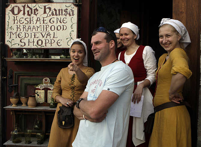 A tourist poses with restaurant staff in Tallinn, Estonia.
