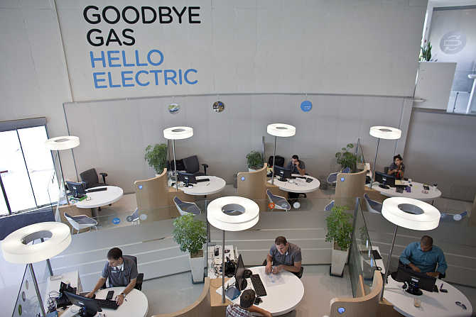 Workers sit at their desks at the headquarters of electric car venture Better Place in Tel Aviv, Israel.