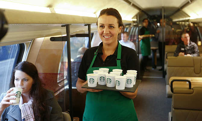 An employee of Starbucks carries a tray with cups of coffee on a train in Zurich, Switzerland.