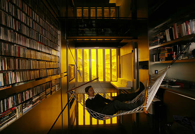 Architect Gary Chang rests in a hammock inside his apartment in Hong Kong.
