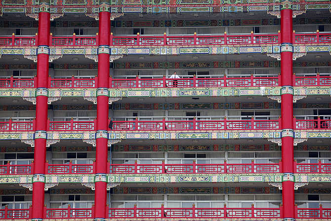 A man stands on a balcony of a building in Taipei, Taiwan.