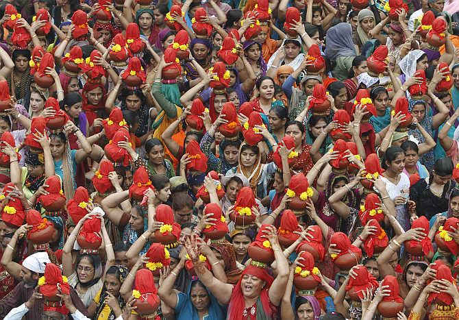 Women carry earthen water pots as they take part in a Jhulelal Chaliha procession in Ahmedabad.