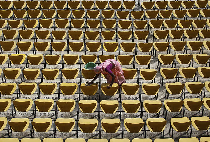 A worker cleans the seats of a stadium in Nagpur.