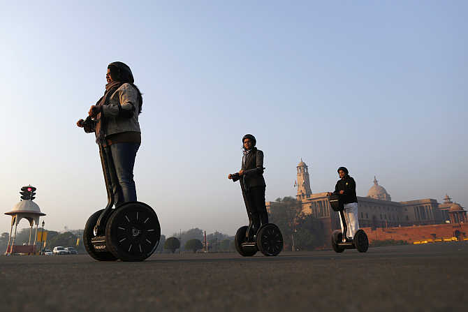 Women ride two-wheeled self-balancing scooters past the Indian Defence Ministry in New Delhi.