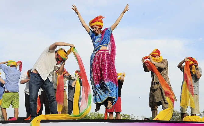 A tourist celebrates after finishing first in a turban tying competition in Jaipur.
