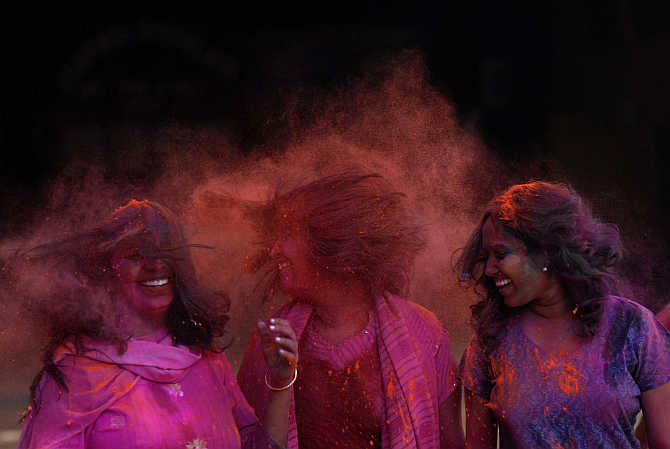Girls react after coloured powder is thrown on them during Holi celebrations in Chennai.