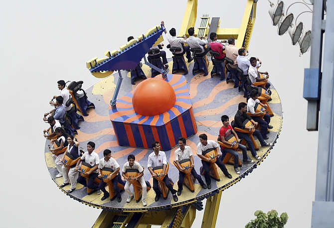 Visitors ride the Mega Disco roller coaster at an amusement park in Noida.